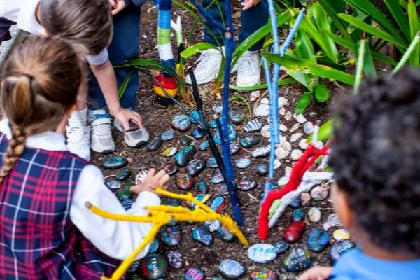 St Andrews Catholic Primary School Malabar - students looking at stones in the school garden