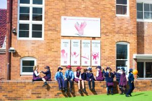 St Andrews Catholic Primary School Malabar - students sitting on bench in front of schools banners